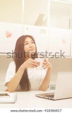 Portrait of Asian student dringking cup of tea or coffee while studying in library with laptop computer. Happy brunette lady looking upwards. Toned image.  - stock photo