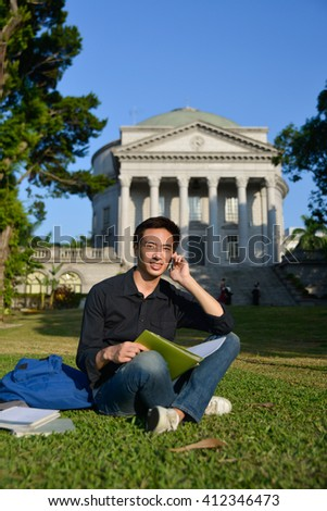 Portrait of asian student use use of the cellphone sitting a grass at a campus - stock photo