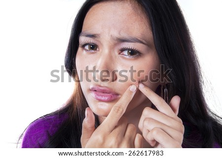 Portrait of asian teenage girl using her finger to clean acne from her face, isolated over white - stock photo