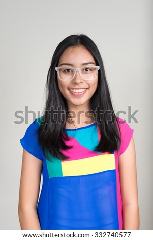 Portrait of Asian teenager girl smiling and wearing white eyeglasses - stock photo