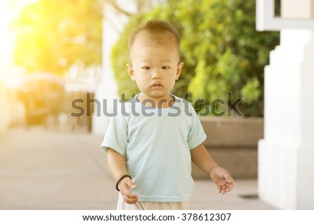 Portrait of Asian toddler walking outdoor in sunset. - stock photo