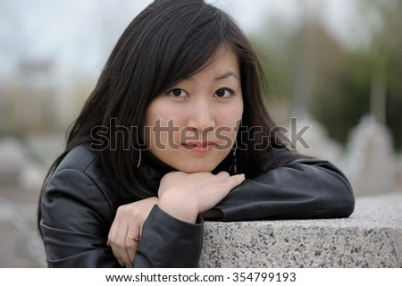 Portrait of asian woman in black jacket at park - stock photo