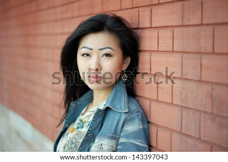 Portrait of asian woman near wall - stock photo