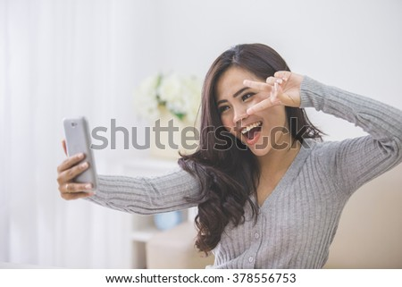 portrait of asian woman take photo of her self using smart phone camera - stock photo
