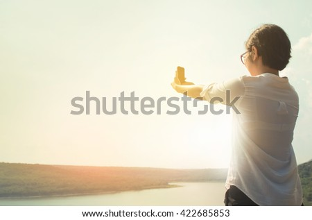 Portrait of asian woman taking a photo with smartphonein natural background. Asian girl looking the nature through her smartphone or cellphone. Woman in natural background with sunset. Vintage stlye. - stock photo