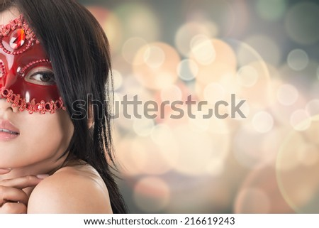 Portrait of Asian young beautiful woman in a carnival mask, closeup portrait. - stock photo