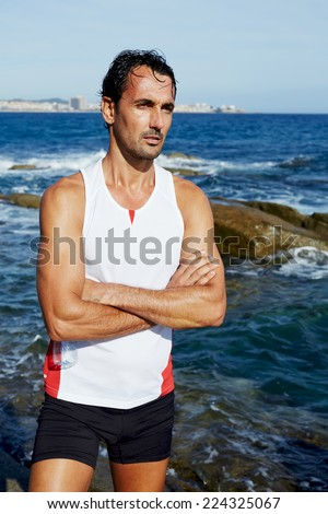 Portrait of athlete standing on sea rocks at sunny summer day while resting after intensive training outdoors, exhausted fit runner after workout resting on seaside, healthy lifestyle concept - stock photo