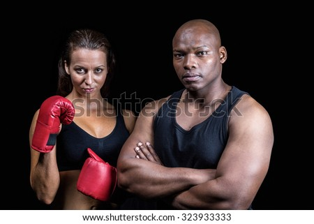 Portrait of athletes standing together against black background - stock photo