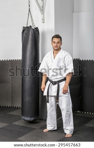 Portrait of athletic black belt karate man standing next to a boxing bag - stock photo