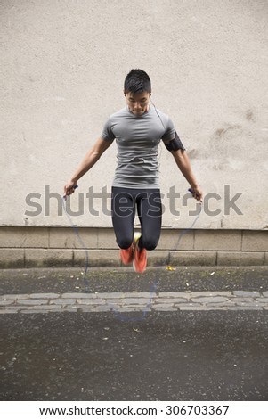 Portrait of athletic Chinese man using a skipping rope in a city street. - stock photo
