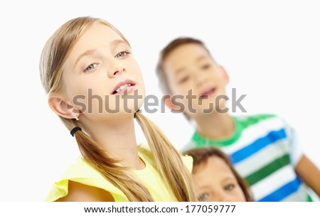Portrait of attentive girl and her classmates listening to the teacher at lesson - stock photo