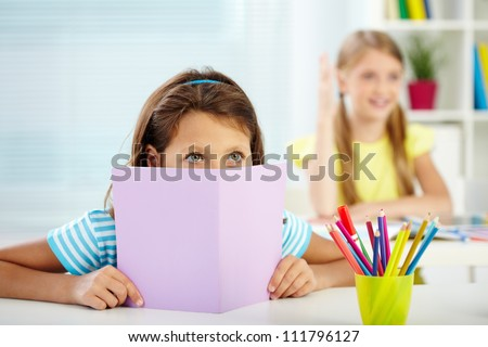 Portrait of attentive girl listening to the teacher at lesson - stock photo