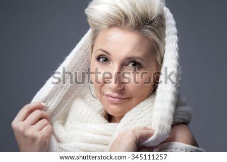 Portrait of attractive adult blonde woman. Studio shot. Winter style. - stock photo