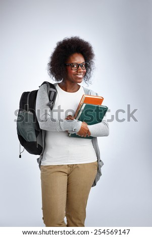 Portrait of attractive african woman with backpack and books over white background - stock photo