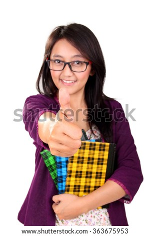 Portrait of attractive Asian girl holding books and giving a thumb up, isolated on white background - stock photo