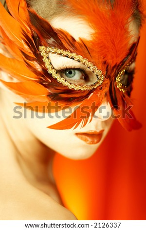 Portrait of attractive beautiful young woman wearing red carnival mask - stock photo