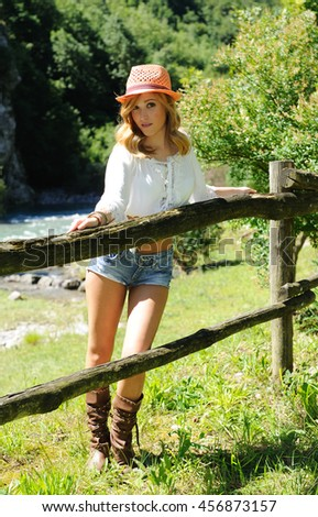 Portrait of attractive blonde on the ranch - stock photo