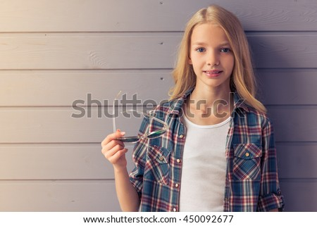 Portrait of attractive blonde teenage girl in casual clothes holding sun glasses, looking at camera and smiling, standing against gray wall - stock photo