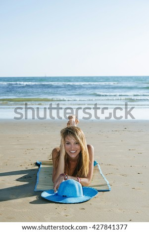 Portrait of attractive blonde woman smiling at camera while lying on mat on beach
