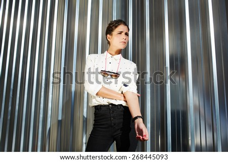 Portrait of attractive brunette hipster woman posing on shiny wall background, fashionable model standing on silver background looking away - stock photo