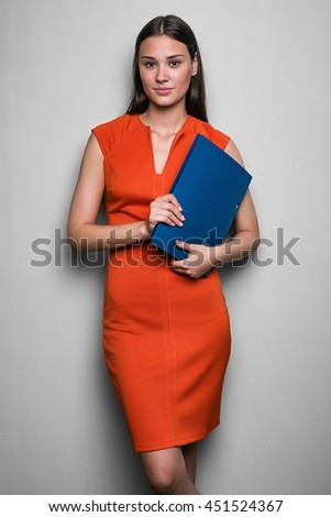 Portrait of attractive brunette in red dress with blue folder looking at camera against of white background.Studio shot, isolate. - stock photo
