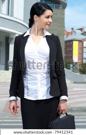 Portrait of attractive business woman in suit carrying laptop - stock photo