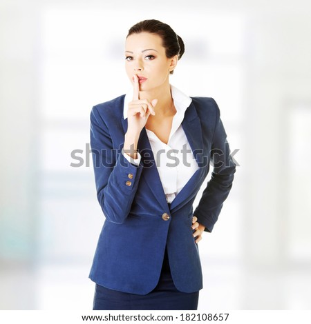 Portrait of attractive business woman with finger on lips, gesturing for quiet  - stock photo