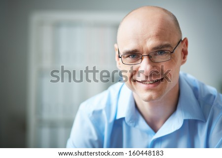Portrait of attractive businessman in eyeglasses looking at camera - stock photo