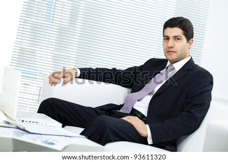 Portrait of attractive businessman in suit sitting in office - stock photo