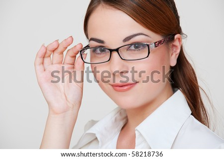 portrait of attractive businesswoman against grey background - stock photo