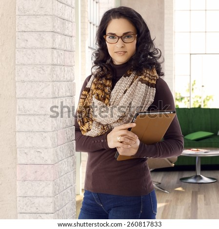 Portrait of attractive businesswoman holding tablet computer, looking at camera. - stock photo