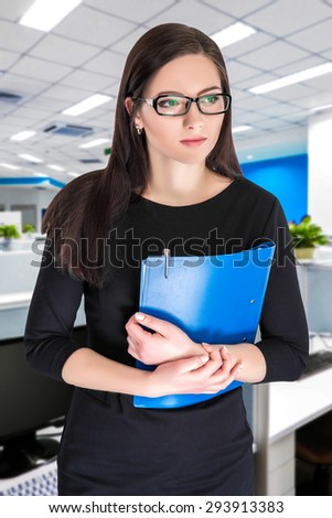 Portrait of attractive businesswoman in glasses with blue folder  - stock photo