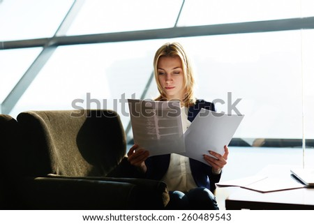 Portrait of attractive businesswoman reading papers or documents sitting in luxury coffee shop next to the window, soft focus, filtered image - stock photo