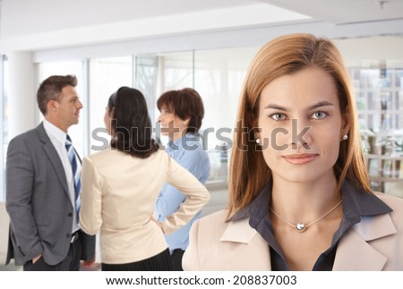 Portrait of attractive caucasian businesswoman with colleagues at office. - stock photo