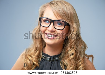 Portrait of attractive caucasian smiling blonde woman studio shot looking at camera wearing glasses - stock photo