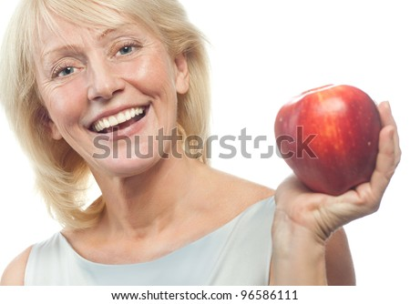 portrait of attractive  caucasian smiling mature woman blond isolated on white studio shot with red apple - stock photo