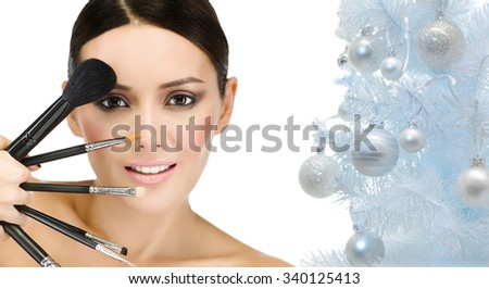 portrait of attractive  caucasian smiling woman brunette isolated on white studio shot brushes makeup christmas new year tree - stock photo