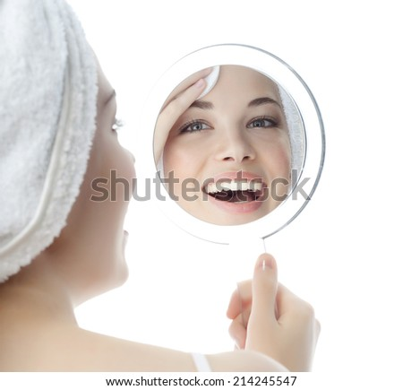 portrait of attractive  caucasian smiling woman isolated on white studio shot cleaning her face looking at the mirror - stock photo