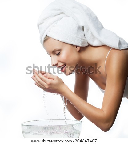 portrait of attractive  caucasian smiling woman isolated on white studio shot washing her face - stock photo