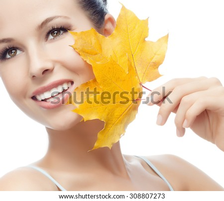 portrait of attractive  caucasian smiling woman isolated on white studio shot with yellow maple leaf - stock photo