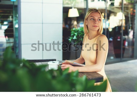 Portrait of attractive caucasian woman enjoying a good day at modern terrace of coffee shop, charming female hipster waiting someone at sidewalk cafe with green plants, businesswoman at coffee break - stock photo
