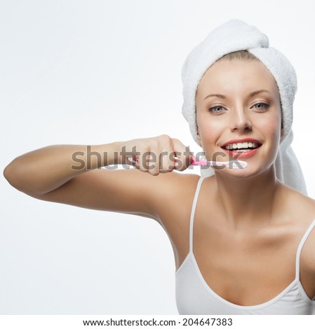 portrait of attractive  caucasian woman  with long blond hair isolated on white studio shot looking at camera with tooth brush - stock photo