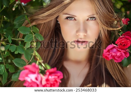 portrait of attractive caucasian  young woman blond with red rose flower - stock photo
