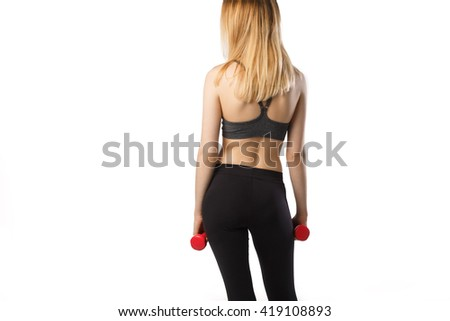 Portrait of attractive cheerful fitness girl in gray top and black leggings with red dumbbells posing over white background isolated back view - stock photo