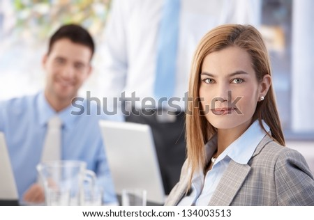 Portrait of attractive confident businesswoman working in busy office, colleagues behind. - stock photo