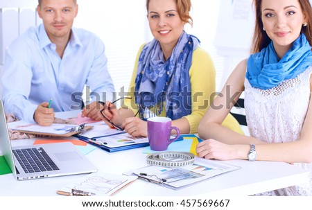 Portrait of attractive designers sitting on desk  in office - stock photo
