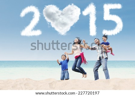 Portrait of attractive family jumping at beach under cloud of 2015 - stock photo