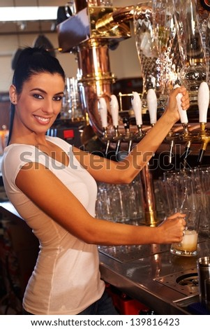 Portrait of attractive female bartender tapping mug of beer in pub, smiling. - stock photo