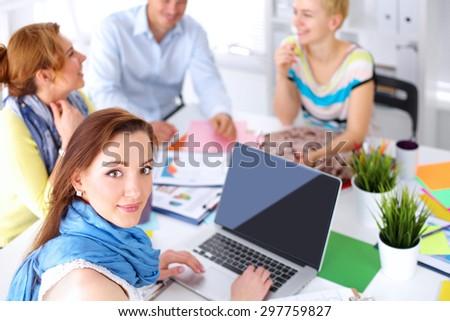 Portrait of attractive female  designer sitting on desk  in office - stock photo