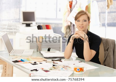 Portrait of attractive female fashion designer sitting at office desk, smiling. - stock photo